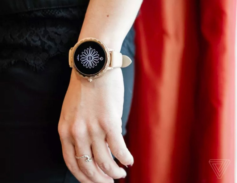 A woman's arm at her side, and she is wearing a health tracking device watch.