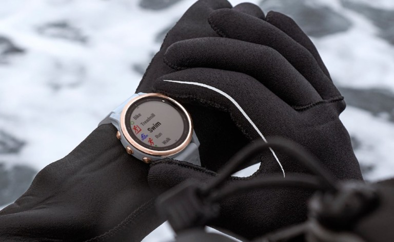 A pair of black-gloved hands, with one hand adjusting a health tracking device watch.