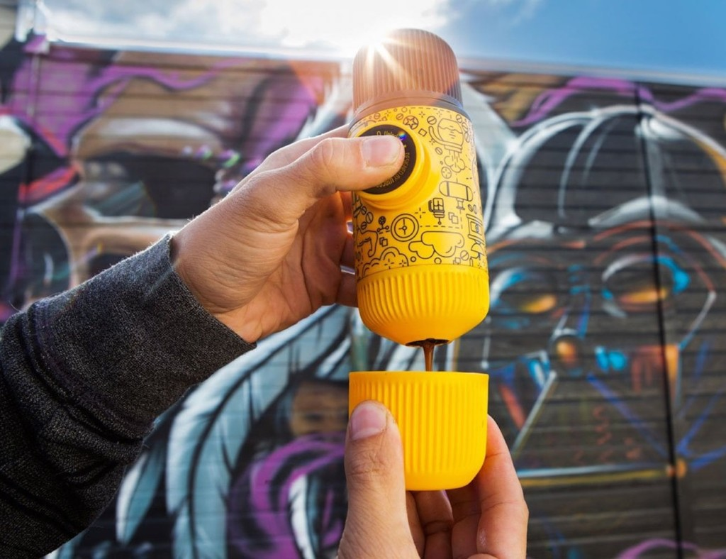 A person holding a yellow handheld espresso maker and pressing a button to deliver espresso into a small yellow cap.