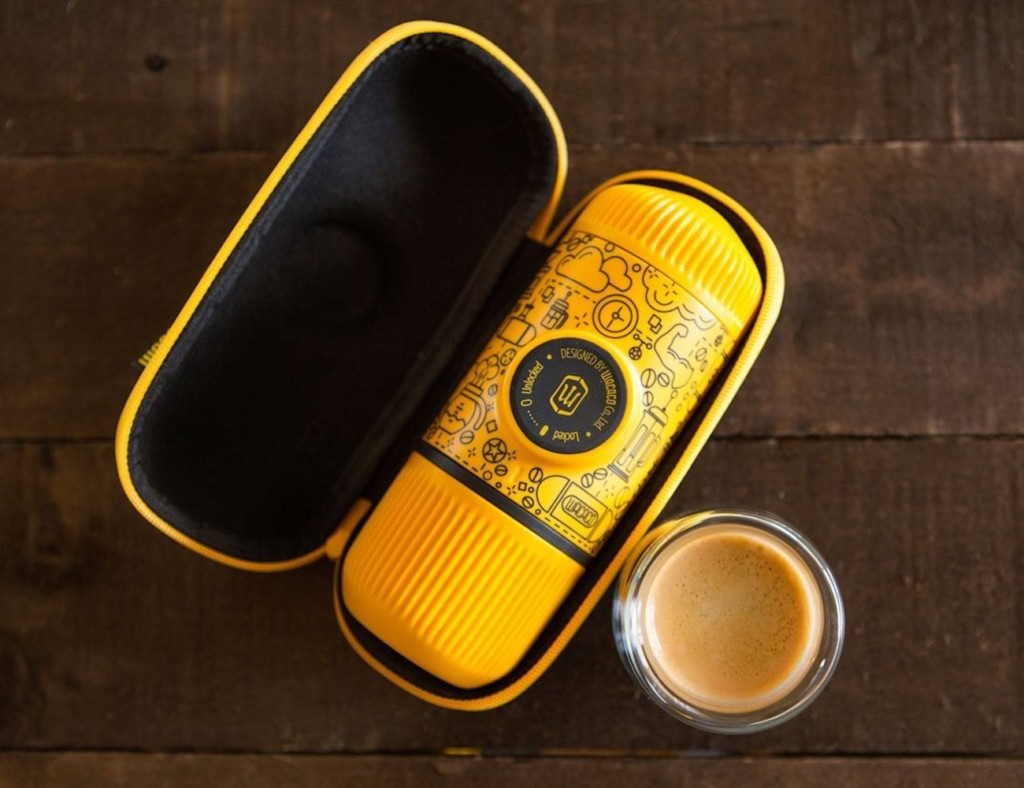 An open case with a small yellow espresso maker in it with a small glass of espresso next to it.