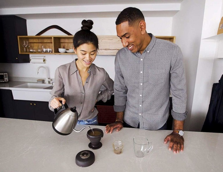 A man and woman standing at a kitchen counter and the woman is pouring water from a kettle into a compact coffee brewer.