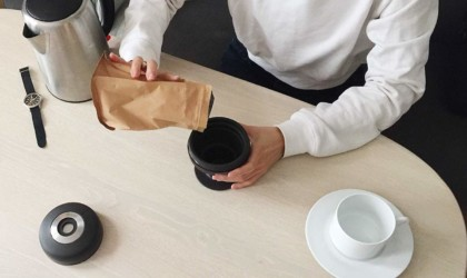 A top down view of a woman pouring coffee grounds into the top of a compact coffee brewer.