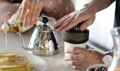 A view of a kitchen counter; a woman is pouring syrup on pancakes, and a man is pressing the top on a compact coffee brewer.