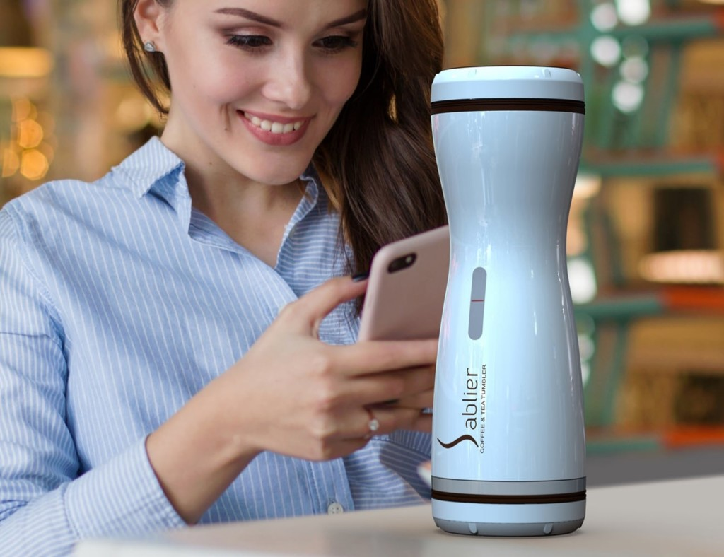 A woman is looking at her phone and smiling with a white compact coffee brewer in front of her.
