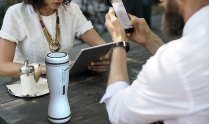 A man and a woman are sitting at a table looking at their personal electronics with a white compact coffee brewer sits between them.
