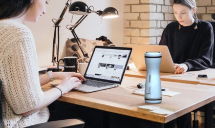 A woman is sitting at her desk working at her laptop with a small white coffee brewing mug beside her.