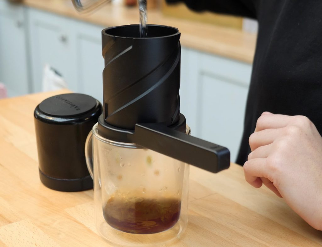 A close up of a person pouring water into a twist press coffee maker.