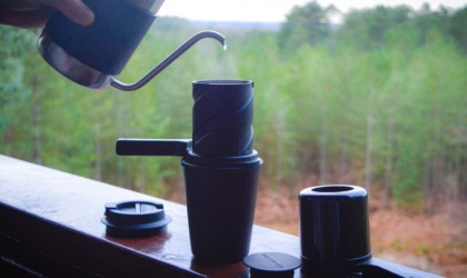A close-up image of the parts of a twist press coffee maker on a deck ledge, while a person pours water into it.