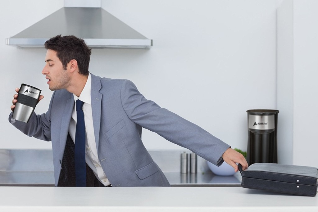A man is grabbing his briefcase from a kitchen counter and is in motion to head out the door, holding a travel mug of coffee and drinking from it.