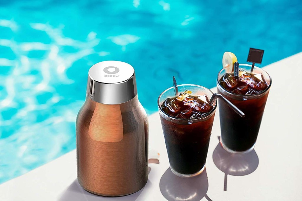 The bottom part of a copper cold-brew coffee maker on a ledge next to a pool, with two glasses of cold brew coffee next to it.