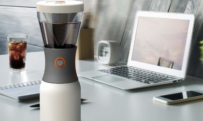 A cold-brew compact coffee brewer is on a white desk next to a laptop and notebook.