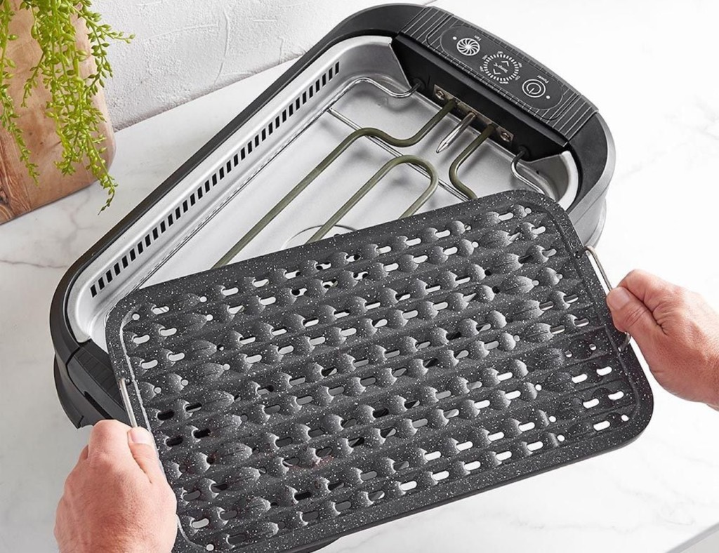 A person removing the grate from an indoor grill kitchen accessories and gadgets.