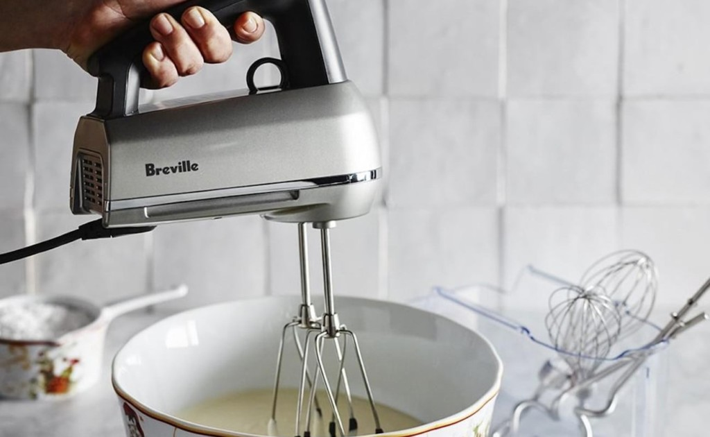 A woman using a kitchen accessories and gadgets hand mixer to beat something in a bowl.