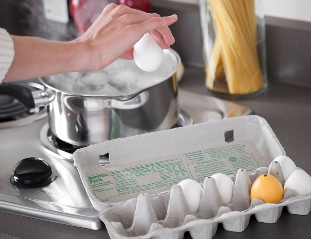A yellow kitchen accessories and gadgets egg timer in a carton with eggs