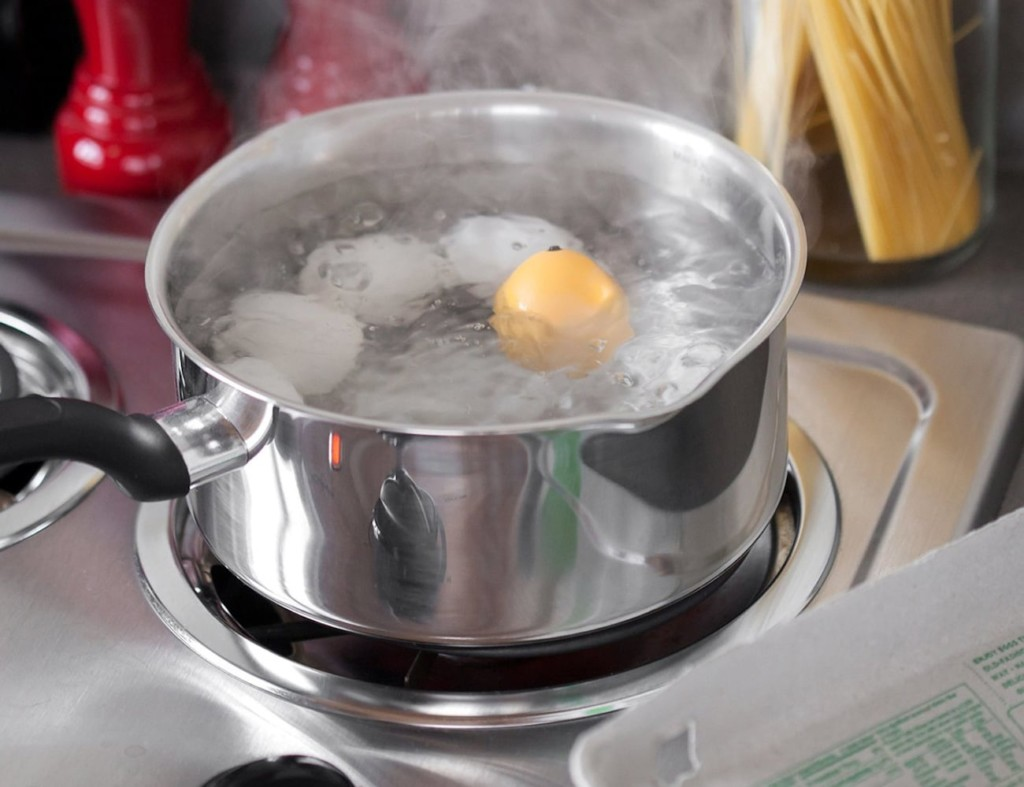 A yellow kitchen accessories and gadgets egg timer in a pot of boiling water with eggs.