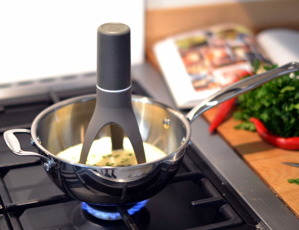 A kitchen accessories and gadgets self-stirring utensil in a pot on the stove.