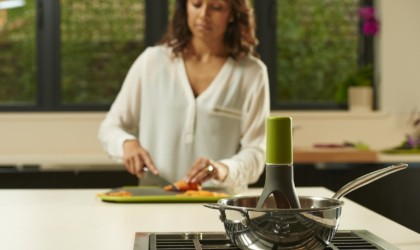 A woman cutting vegetables in the background while a self-stirring kitchen accessories and gadgets is in a pot in the foreground.