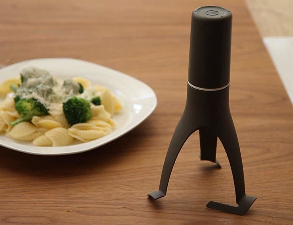 A self-stirring kitchen accessories and gadgets on a counter next to a plate of pasta.
