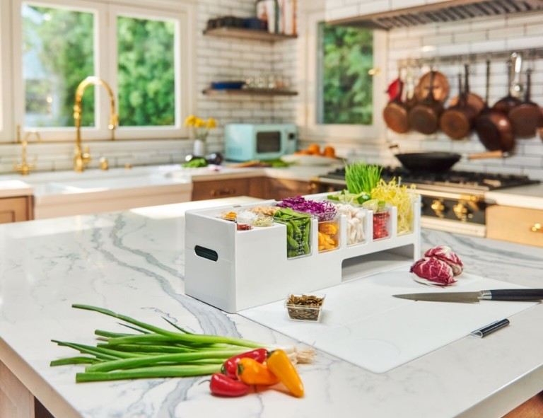 A kitchen accessories and gadgets prep deck on a kitchen counter, filled with vegetables.