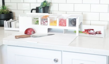 A white kitchen accessories and gadgets prep deck on a counter, with a knife in front and veggies in it.