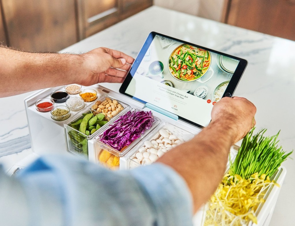 A man placing a tablet on top of a kitchen accessories and gadgets prep deck that is filled with vegetables.