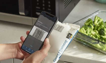 A person holding a smartphone and using a kitchen accessories and gadgets microwave app.
