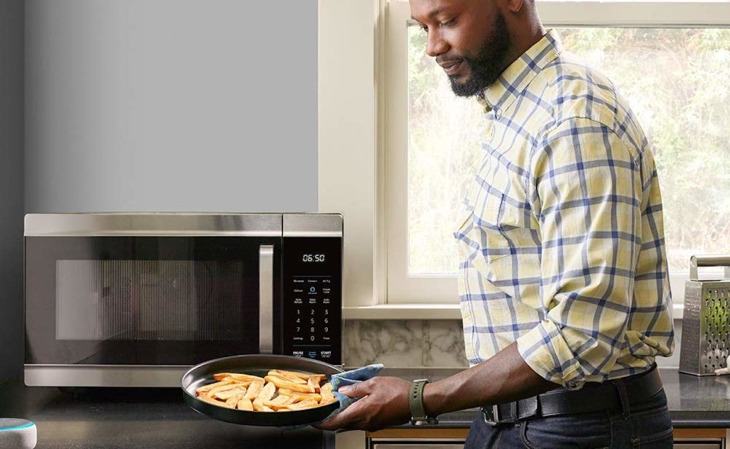 A man holding a plate of food in front of a kitchen accessories and gadgets smart microwave.