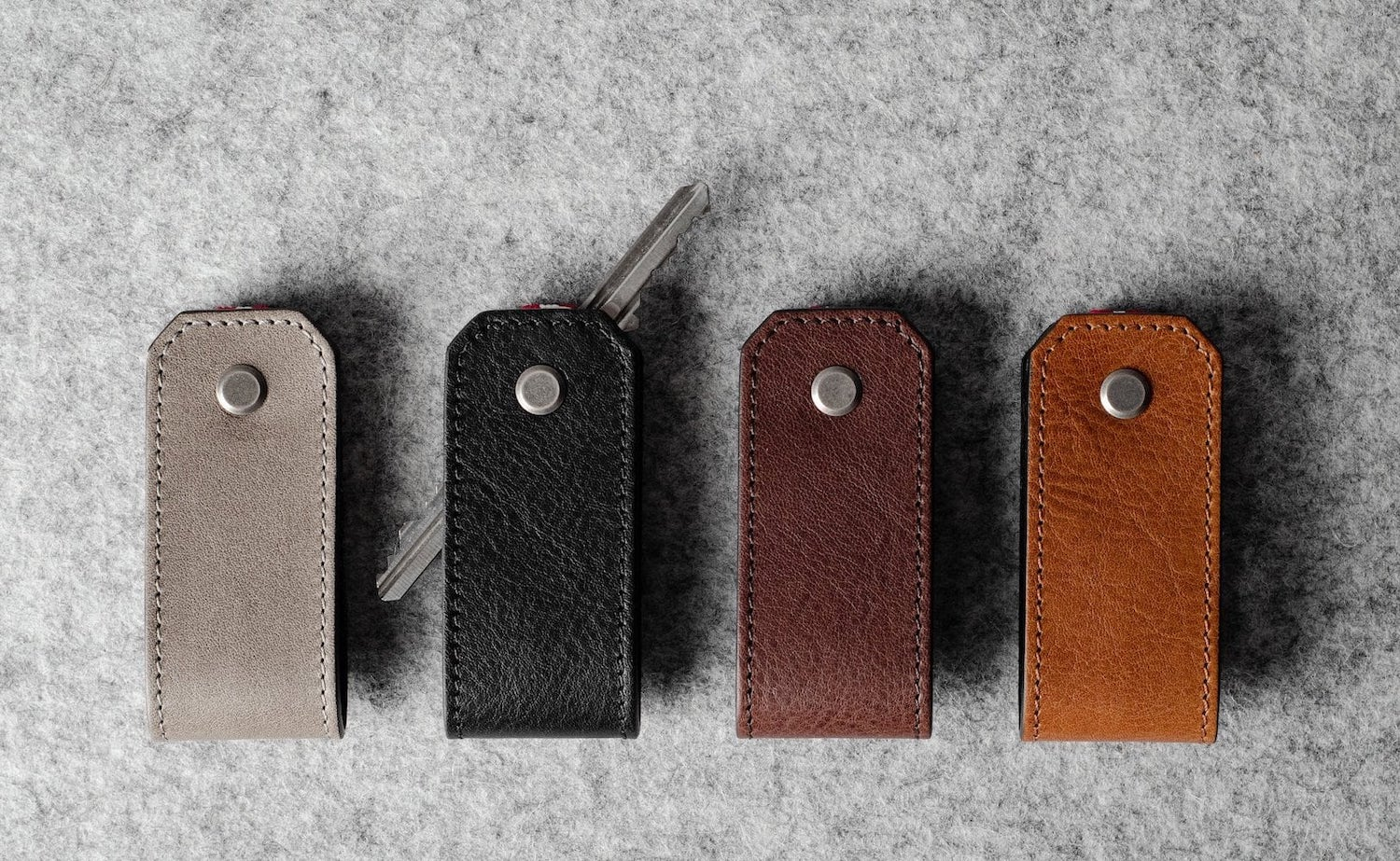 Four of the leather holders, one of which has two keys poking out of it