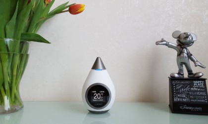 A white thermostat shaped like a teardrop is sitting on a counter next to flowers and a Mickey Mouse statue.