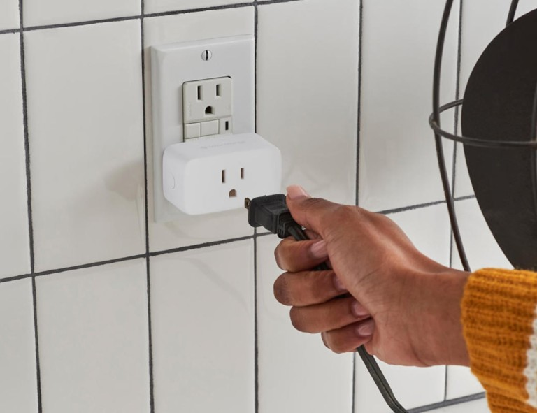 A persons is plugging a cord into a smart plug in a wall outlet.