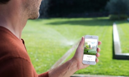 A man is in his backyard looking at a sprinkler system app on his smartphone.