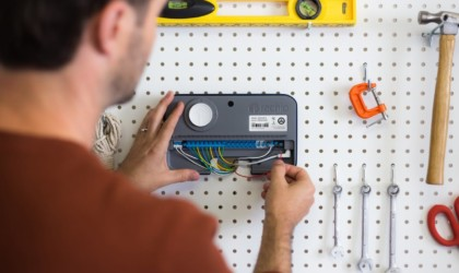 A man is wiring a sprinkler system monitor on his garage wall.