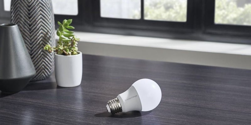 A smart light bulb is sitting on a dark wood table.