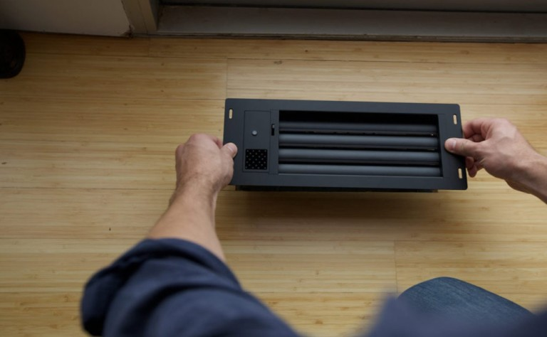 A person is setting an air vent on a light wood floor.
