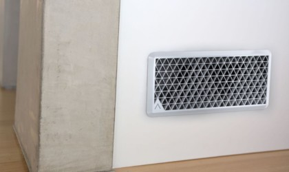 A white air vent add-on is in a white wall.
