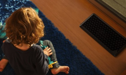 A child is sitting on a blue rug with a black air vent on the floor in front of them.