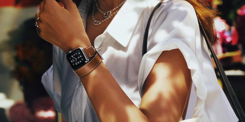 Woman in white wearing leather Hermes apple watch strap