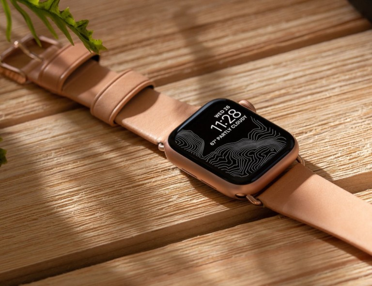 Close up of apple watch with brown leather strap on wood surface