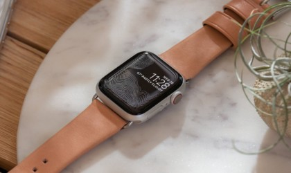 closeup of apple watch with leather strap on marble table