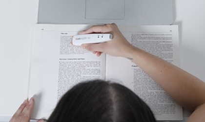 Overhead view of someone using scanning device over text