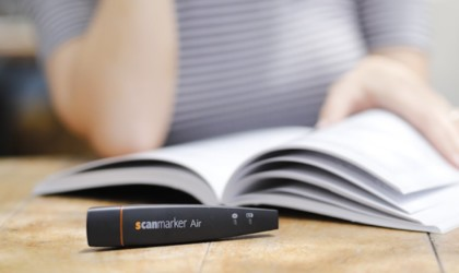 Close up of scanning device on a desk with a book behind it