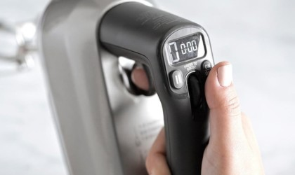 Close up of person operating hand mixer