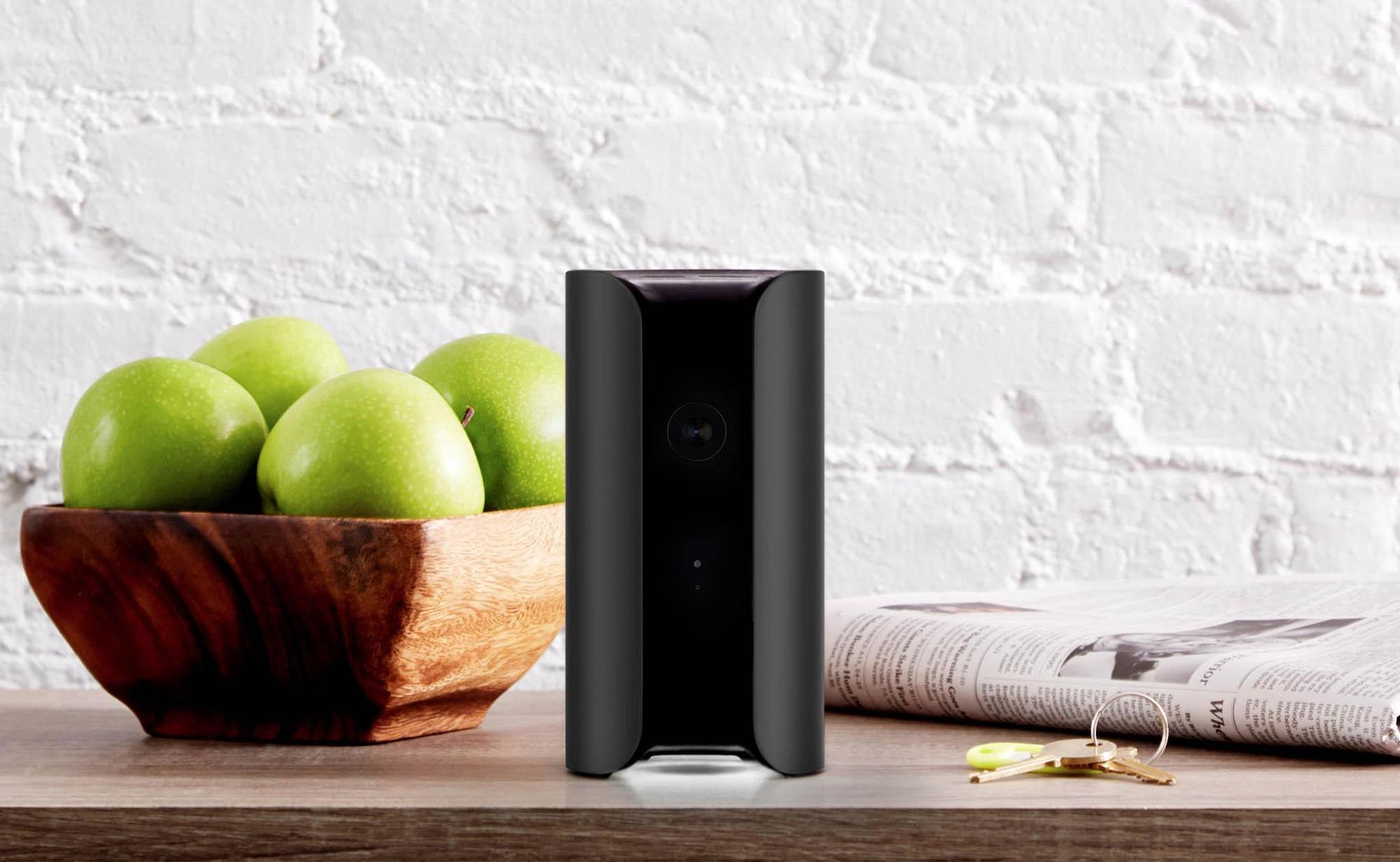 The all-in-one home security camera is on a counter with a bowl of green apples behind it.