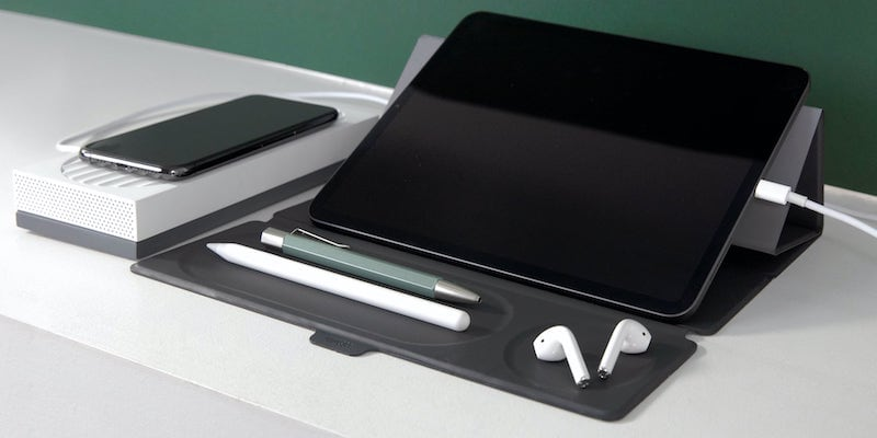 A mobile office setup on a white desk with a tablet, pens, and AirPods.