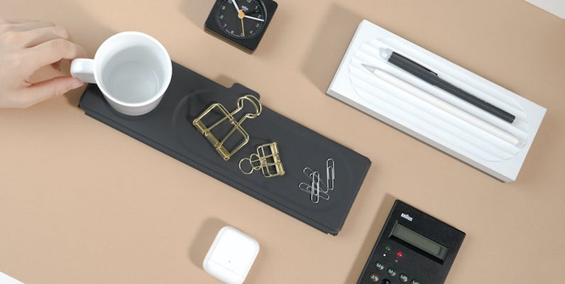 A top-down view of office supplies on a black mobile office mat.