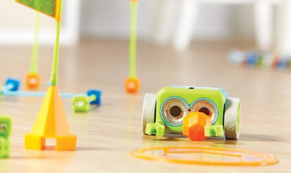 The coding robot activity set is on a wood floor.