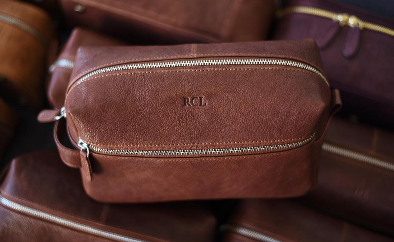 The leather toiletry bag is personalized on top of other bags.