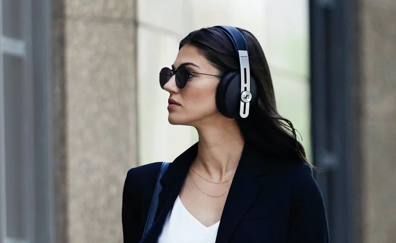 A woman is wearing the modern headphones while walking on the street.