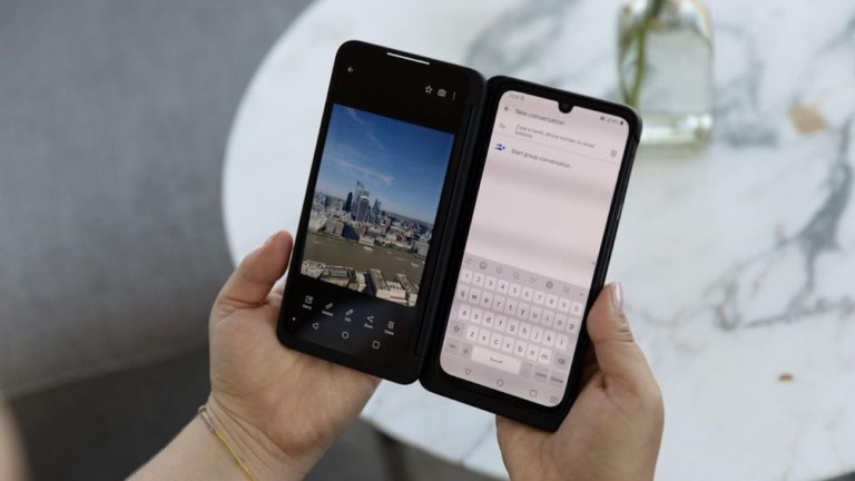 A person is holding a dual-screen phone with a picture on one screen and a text message on the other screen.