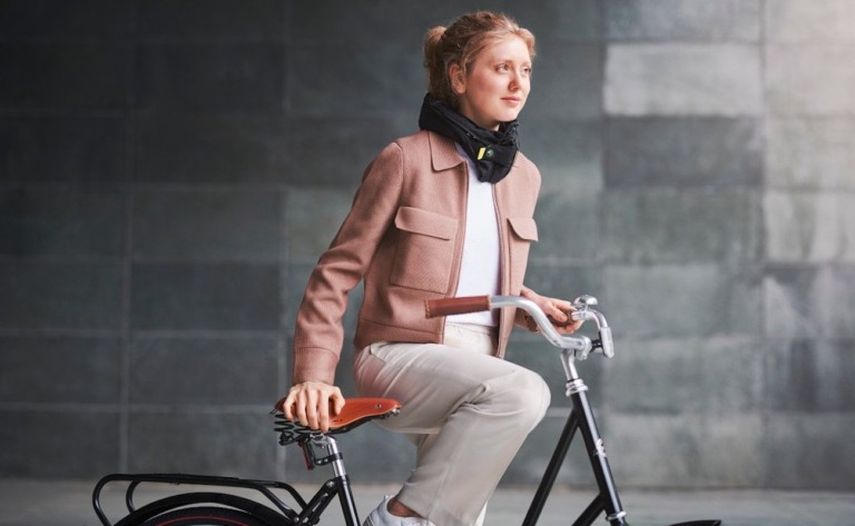 A woman is getting onto a bicycle, and she is wearing a black airbag around her neck.